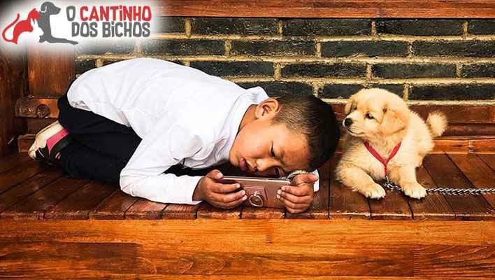 Criança no celular e com cão do lado - cachorro pode ajudar